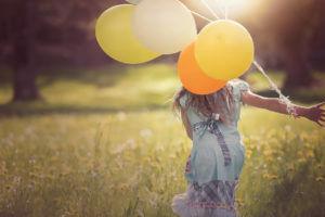 Õhupallidega tüdruk aasal