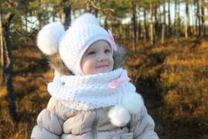 Valge mütsiga pisike tüdruk rabas
