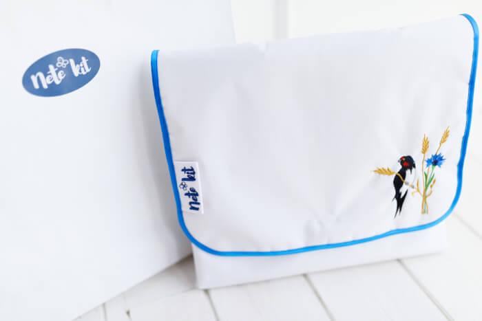 Sinise servaga valge tikitud pääsuksestega mähkimiskott-alus