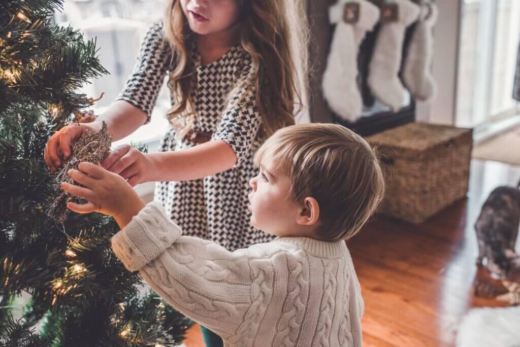 poiss ja tüdruk ehivad kuusepuud